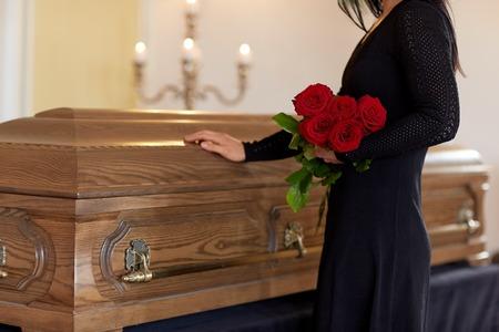 traurige Frau mit roten Rosen und Sarg am Begräbnis