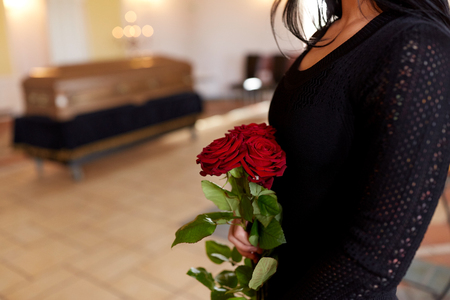 close up of woman with roses and coffin at funeral Stock Photo
