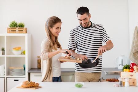 가정에서 부엌에서 음식을 요리하는 부부 스톡 콘텐츠