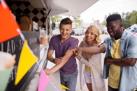 customers or friends choosing menu at food truck Stock Photo