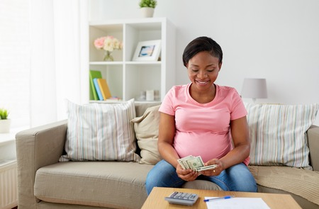 happy pregnant woman counting money at home