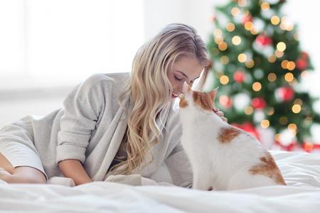 クリスマス時にベッドで猫と幸せな若い女