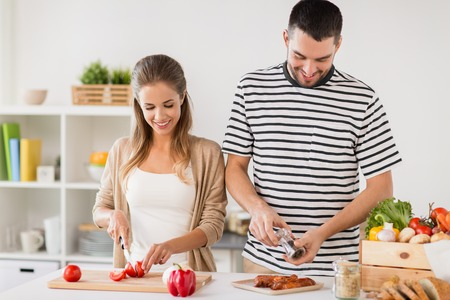 happy couple cooking food at home kitchen