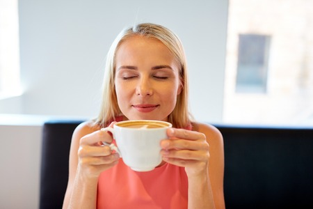 close up of woman drinking coffee at restaurant