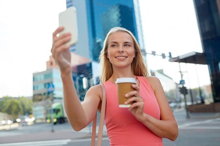 woman with coffee taking selfie by smartphone