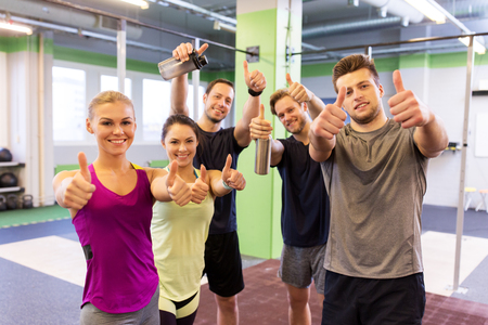 group of happy friends in gym showing thumbs up