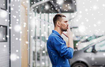 auto mechanic smoking cigarette at car workshop Stock Photo