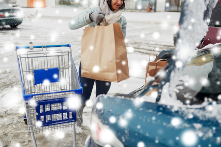 consumerism: customer loading food from shopping cart to car