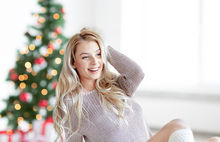 happy young woman stretching in bed at christmas