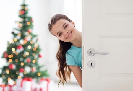 自宅のドアの後ろに幸せな笑みを浮かべて美しい女の子