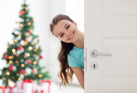 happy smiling beautiful girl behind door at home Imagens
