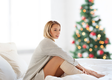 happy young woman sitting in bed at christmas
