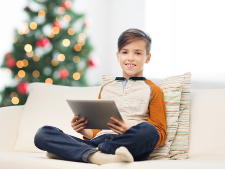 niños platicando: smiling boy with tablet pc at home at christmas