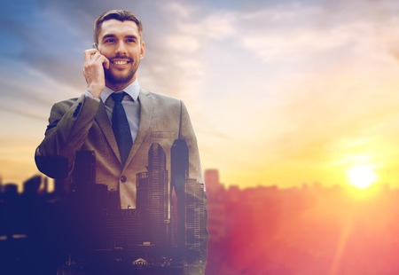 smiling businessman with smartphone outdoors Banque d'images