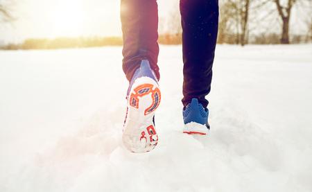 close up of feet running along snowy winter road