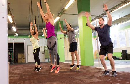 group of people exercising and jumping in gym