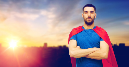 man in red superhero cape over city background