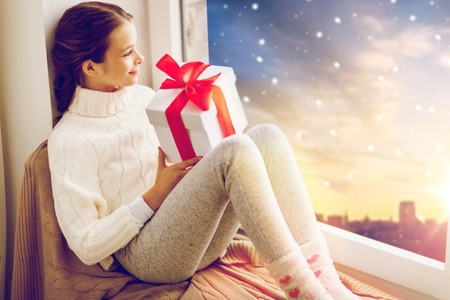 girl with christmas gift on window sill in winter