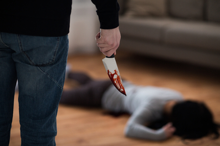 criminal with knife and dead body at crime scene Foto de archivo