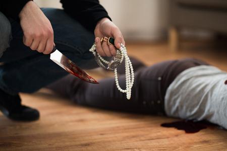 Criminel avec couteau et bijoux sur scène de crime Banque d'images - 89984512