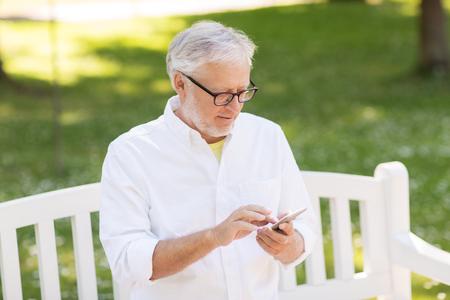 senior man with smartphone at summer park