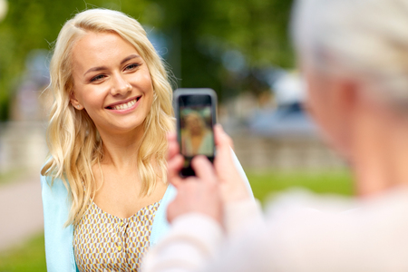senior mother photographing daughter by smartphone Banque d'images