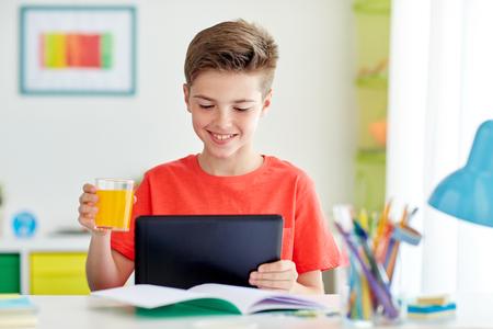 chico estudiante con tablet pc y jugo en casa
