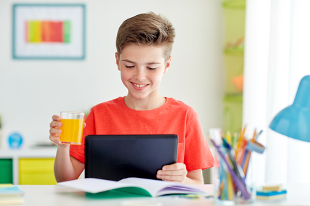 student boy with tablet pc and juice at home