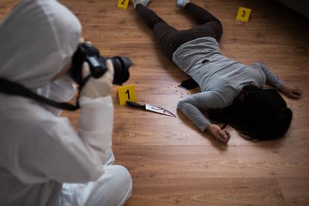 criminalist photographing dead body at crime scene Stock Photo