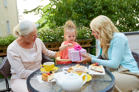 happy mother giving present to little daughter at cafe