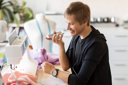 fashion designer with smartphone working at studio