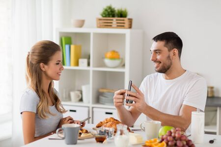couple with smartphones having breakfast at home Banque d'images