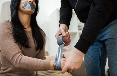 criminal tying woman with adhesive tape