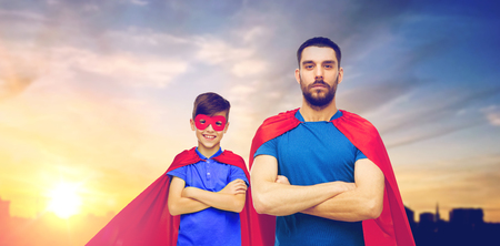 father and son in superhero capes over city
