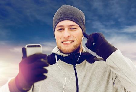 happy man with earphones and smartphone in winter Stock Photo