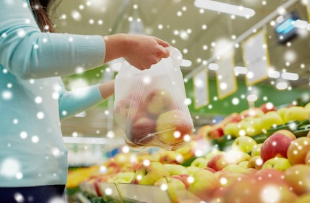 consumerism: woman with bag buying apples at grocery store