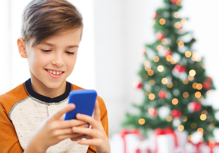 close up of happy boy with smartphone at christmas Stock Photo