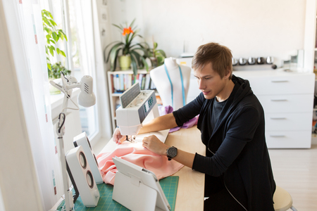 fashion designer with tablet pc sewing at studio