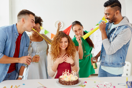 happy coworkers with cake at office birthday party