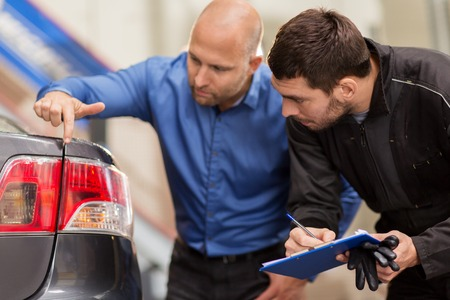 mechanic and customer looking at car taillight Stok Fotoğraf