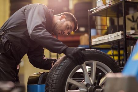 Automechaniker , der Autorad an der Werkstatt überprüft
