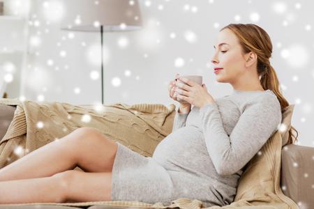 gelukkige zwangere vrouw met een kopje thee te drinken thuis Stockfoto
