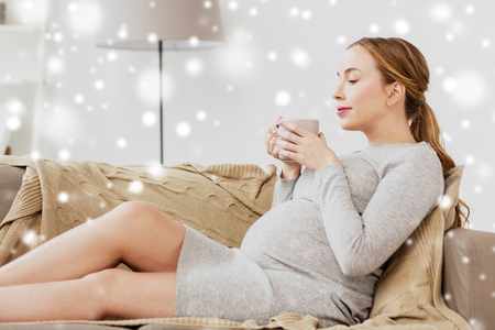 happy pregnant woman with cup drinking tea at home