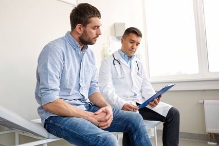 doctor and man with health problem at hospital Banque d'images