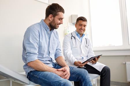 arts met tablet pc en mannelijke patiënt in het ziekenhuis