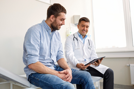 doctor with tablet pc and male patient at hospital