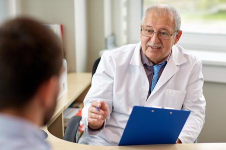 senior arts praten met mannelijke patiënt in het ziekenhuis