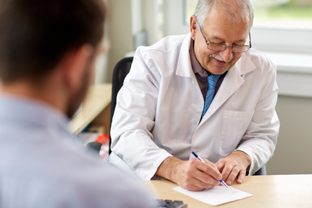 doctor writing prescription for patient at clinic Standard-Bild
