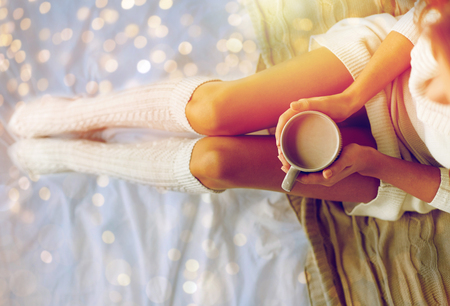 close up of woman with cocoa cup in bed at home