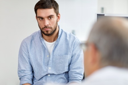 young male patient talking to doctor at hospital Stock Photo